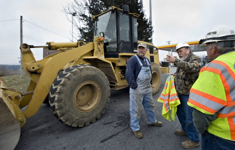 Gary Bly, left, a hired contractor for T.M. Dellinger Trucking, chats with VDOT superintendent Charles Whittington, center, and transportation operator Jeff Oczkowski, both from the Toms Brook area headquarters, about their duties at the 298 exit from Interstate 81 in Strasburg on Friday morning.  Rich Cooley/Daily